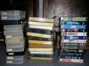 Three piles of VHS tapes and cases